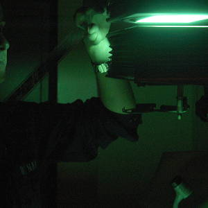A photographic darkroom lit with green light.