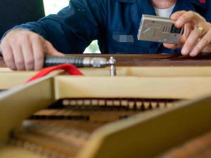 A piano tuner adjusts the tension of piano strings with a tuning hammer in one hand an electronic tuner in the other.