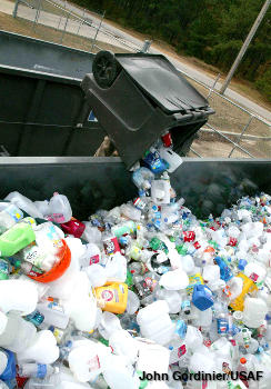 Plastic bottles being tipped into a large recycling dumpster