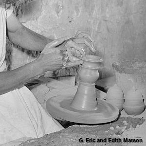 A potter throwing a pot on a wheel