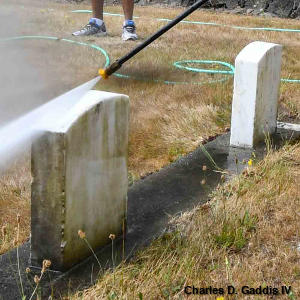 Cleaning memorial headstones with a high-pressure power washer
