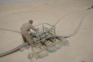 Man operating a pump in the desert