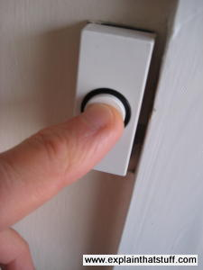 A finger pushing on the doorbell outside someone's house.