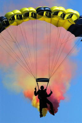 A skydiver pilots a steerable ram-air parachute, giving off colored smoke for effect.