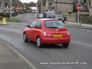 Red car turning left around a curve