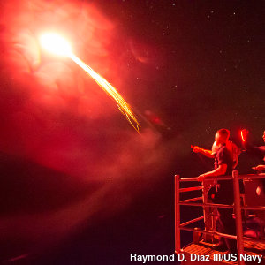 A red distress flare being fired from a ship into the dark night sky.