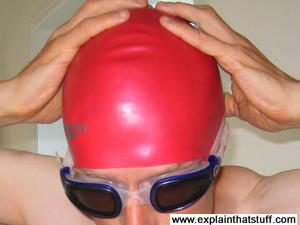 Red latex Speedo swimming cap worn by a swimmer with dark tinted goggles