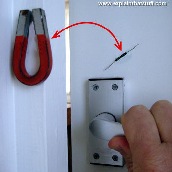 A reed switch mounted on a door and a magnet on the frame to simulate a burglar alarm