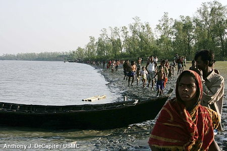 People waiting for aid by a riverbank in Bangladesh, 2007.