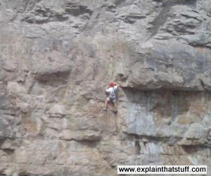 A rock climber gripping a rough cliff face