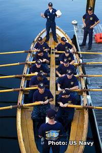 Sailors sitting with oars inside a wooden row boat.