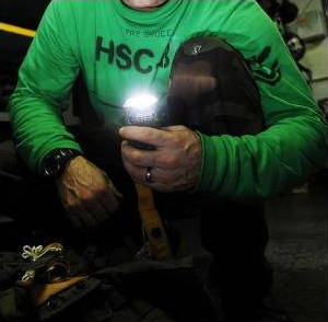 Scuba diver testing emergency strobe light.