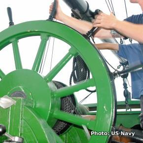 A sailor steers a ship by turning the spokes of a large wooden wheel.