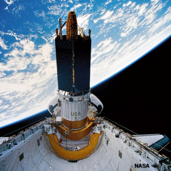 The Space Shuttle launching a communications satellite from its payload bay.