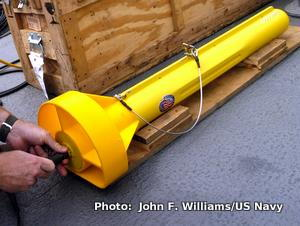 A yellow side-scan sonar towfish being prepared for use on the deck of a ship.