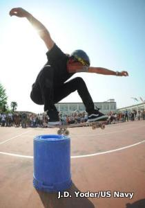 A skateboarder jumps over a large plastic drum.