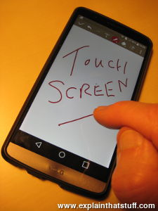 Writing the words 'touch screen' in red ink on a handheld smartphone touchscreen.