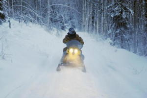 Photo of a snowmobile racing down a snowbound road in Alaska.