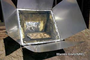 A panel-reflector type of solar cooker being used to bake cookies.