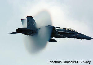 Jet airplane: sonic boom and visual mist created as a fighter jet breaks the sound barrier