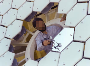 An optical physicist checks the surface of a large space telescope mirror made from many individual hexagonal mirror elements.