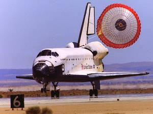 Space Shuttle Endeavor coming in to land in 2002 with a drag chute stretched behind it.