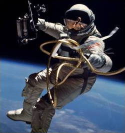 Astronaut Ed White space walking in a space suit with a gold-plated visor helmet.