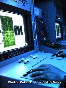 A technician looks at a sonar screen onboard the ship USS Gladiator.