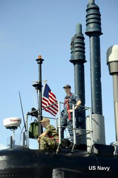 Two naval officers stand on a submarine sail or tower surrounded by communications and navigations antenna.