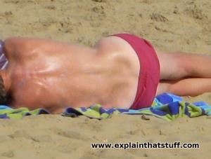 The tanned or sunburned back of a person lying on a beach.