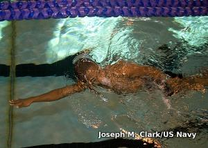Swimmer reaching arm forward as far as possible during front crawl.