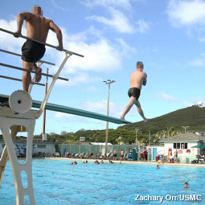 A swimming pool spring diving board made from aluminum with a man jumping off