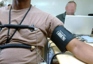A subject strapped to a chair taking a polygraph test.