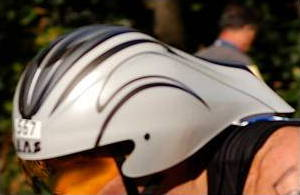 Chrono-style teardrop bicycle helmet worn by a triathlon rider.