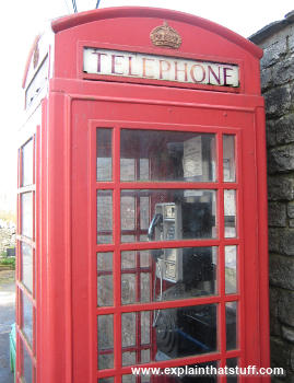 Red village telephone box with a black and silver telephone inside.
