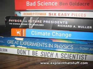 A stack of science books on a brown wooden table.