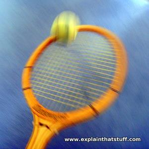 A tennis racket hits a ball into the air with motion blur.