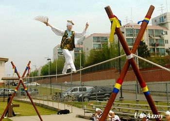 A woman balancing with a fan demonstrates Eoreum, tightrope dancing, in Korea.