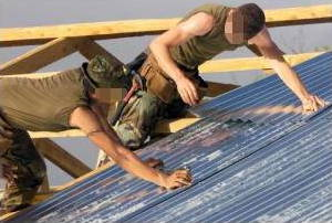 Two marines put a tin roof on a school house.