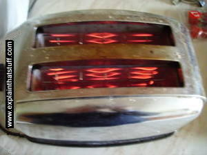 Photo of red hot nichrome ribbon heating elements inside a toaster.