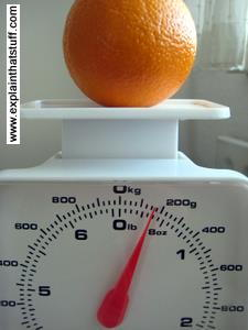 An orange on top of simple kitchen scales.