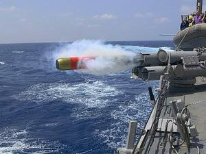 A torpedo fires from the deck of a warship