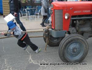 A boy pulls a tractor with a rope