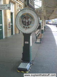 Large mechanical weighing scales on a railroad station.