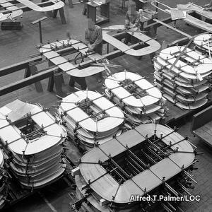 Black and white photo showing a factory making oval formers to hold the copper wires in electricity transformers.