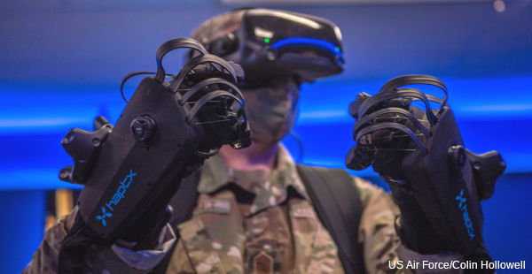A US Air Force officer tests HaptX virtual reality datagloves and a headset.