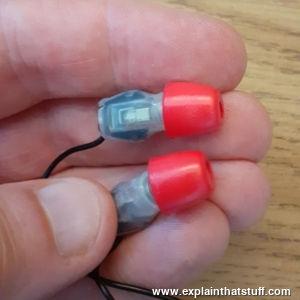 Red viscoelastic earplugs on noise-cancelling earbud headphones
