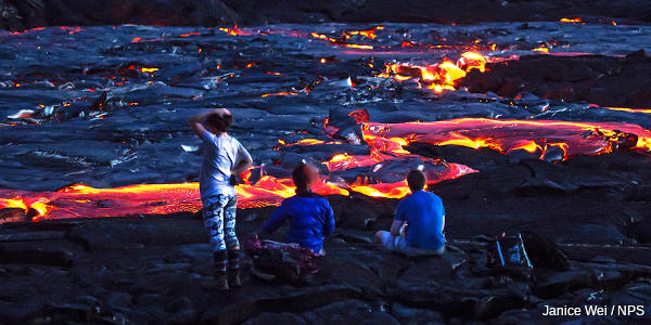 Three people watch the red and yellow hot lava from a volcano in Hawaii.