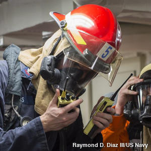 A fireman in a red protective helmet and blue overalls tests a pair of walkie talkies.