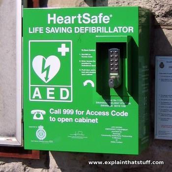 A green defibrillator locked in a box, mounted on the wall of a railroad station.